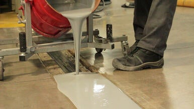 Waterproofing coating poured into an expansion joint opening