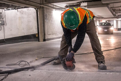 Construction worker sanding expansion joint