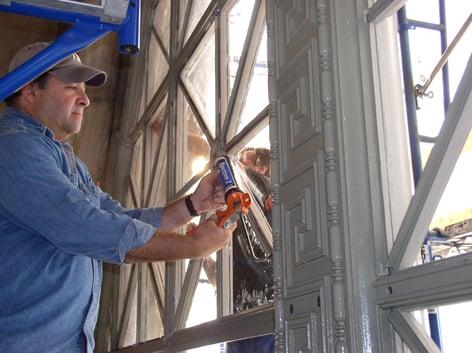 Installer applying sealant to window